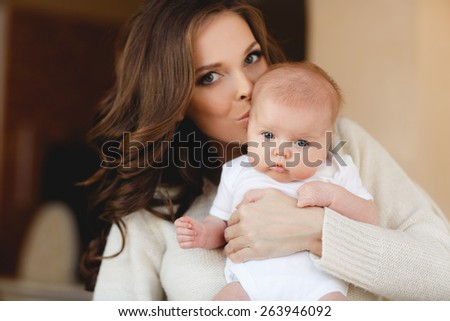 Portrait of happy mother and baby. Portrait of happy young attractive mother lying with her baby on the bed at home. Happy child near to mum in her room - stock photo