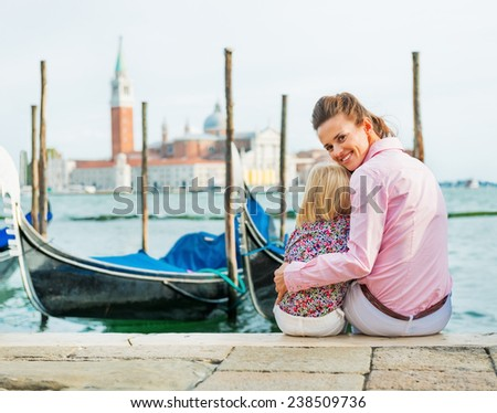 Portrait of happy mother and baby sitting on grand canal embankment in venice, italy - stock photo