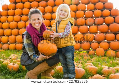 Portrait of happy mother and child choosing pumpkins - stock photo