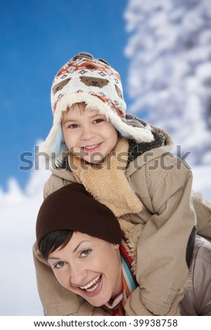 Portrait of happy mother and child  together in snow on a cold winter day laughing, smiling.