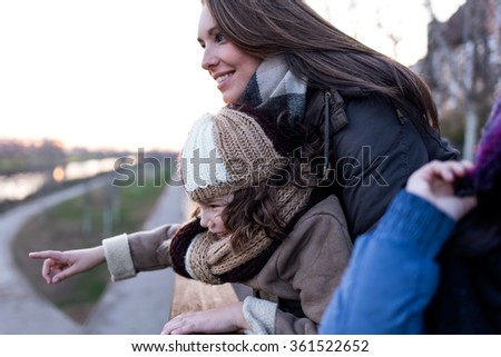 Portrait of happy mother and daughter having fun in the street. - stock photo