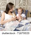 portrait of happy mother and daughter in bed laying reading playing talking - stock photo