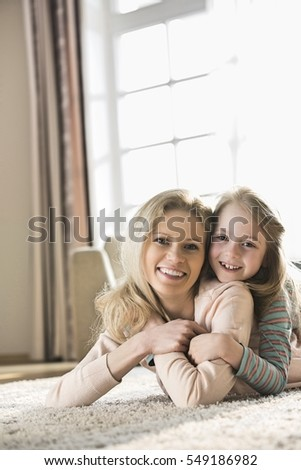 Portrait of happy mother and daughter lying on floor at home
