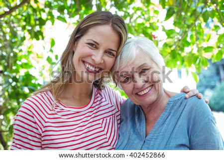 Portrait of happy mother and daughter standing outdoors - stock photo