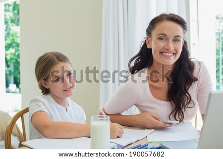 Portrait of happy mother and daughter working at table in huse