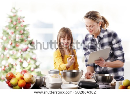 Portrait of happy mother and her cute daughter baking together at home in christmas time.