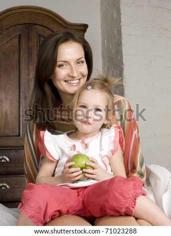 portrait of happy mother and her daughter hugging and smiling eating green apple