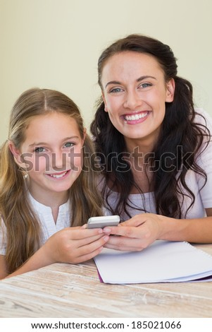 Portrait of happy mother and holding mobile phone at table in house - stock photo