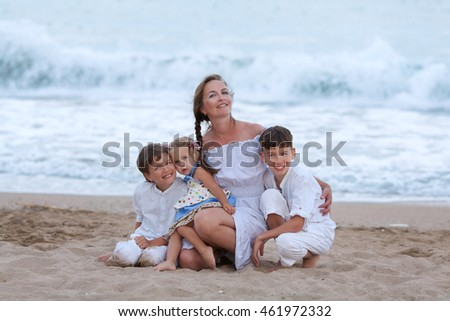 Portrait of happy mother, daughter and sons on beach, outdoor, Spain