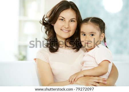 Portrait of happy mother holding her daughter and both looking at camera - stock photo