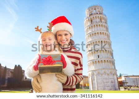 Portrait of happy mother in Christmas hat hugging daughter wearing funny reindeer antlers and holding gift box in front of Leaning Tour of Pisa, Italy. They spending exciting Christmas time traveling. - stock photo