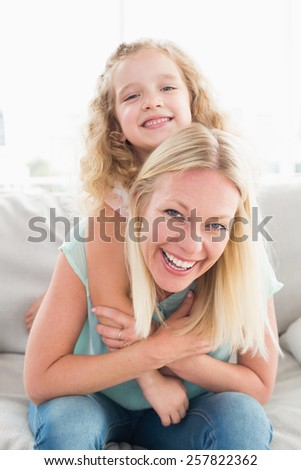 Portrait of happy mother piggybacking daughter on sofa at home - stock photo