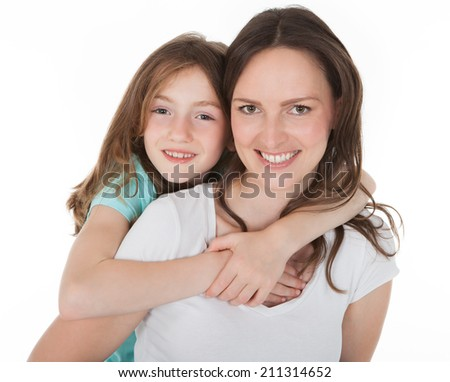 Portrait of happy mother piggybacking daughter over white background