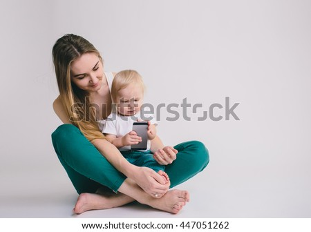 Portrait of happy mother with her little baby isolated on white background. Children's educational games on mobile phones. - stock photo
