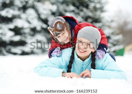 Portrait of happy mother with little child son boy and in winter outdoors - stock photo