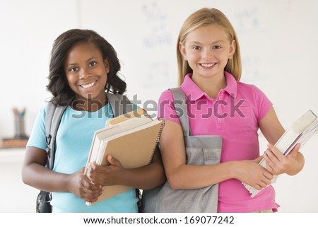 Portrait of happy multi-ethnic schoolgirls with books and bags in classroom - stock photo