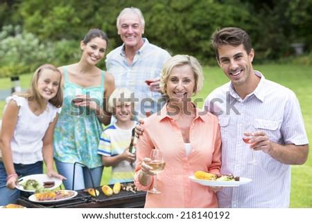 Portrait of happy multi-generation family enjoying barbecue and wine - stock photo