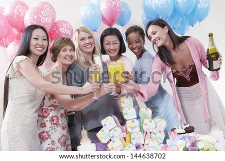 Portrait of happy multiethnic friends having a toast at baby shower - stock photo