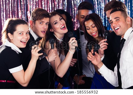 Portrait of happy multiethnic friends singing into microphones at karaoke party - stock photo