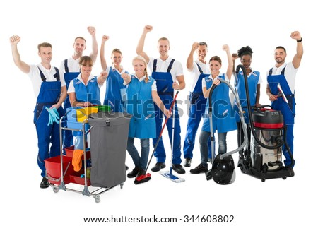 Portrait of happy multiethnic janitors with arms raised holding cleaning equipment against white background - stock photo