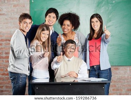 Portrait of happy multiethnic students and professor gesturing thumbsup at desk in classroom - stock photo