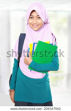 Portrait of happy muslim kid student holding books
