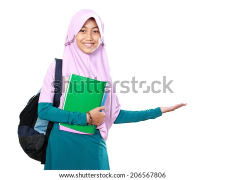 Portrait of happy muslim kid student holding books presenting something on white background