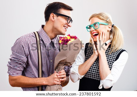 Portrait of happy nerdy couple.Young nerdy man is going to give a bouquet of flowers to his nerdy lady and she is very excited,Flowers for my nerdy lady! - stock photo
