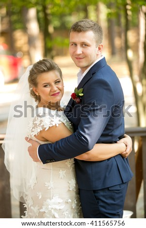 Portrait of happy newly married couple hugging and looking at camera - stock photo