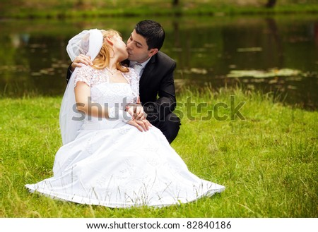 Portrait of happy newlyweds kissing on grass in park - stock photo