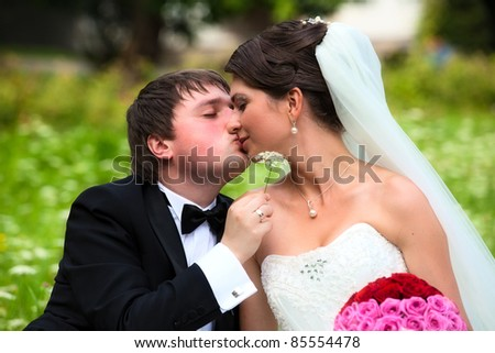 Portrait of happy newlyweds on grass in park