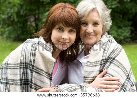 Portrait of happy old woman with her daughter looking at camera and smiling - stock photo