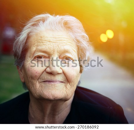 Portrait of happy older lady outdoors - stock photo