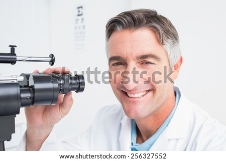 Portrait of happy optician using slit lamp in clinic - stock photo