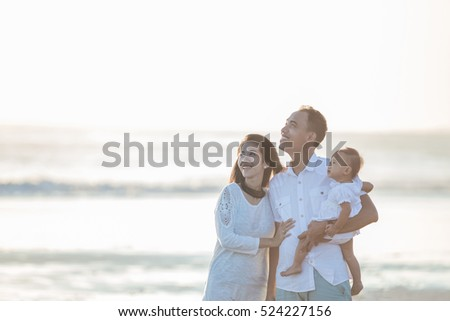 portrait of happy parent with cute baby at the beach having fun together