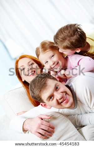 Portrait of happy parents and their children lying on the sofa