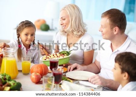 Portrait of happy parents and two children sitting at festive table and going to eat mashed potatoes - stock photo