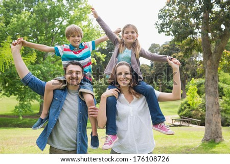 Portrait of happy parents carrying kids on shoulders at the park - stock photo