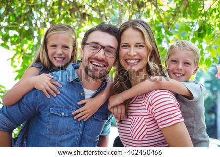 Portrait of happy parents giving piggy back to children - stock photo