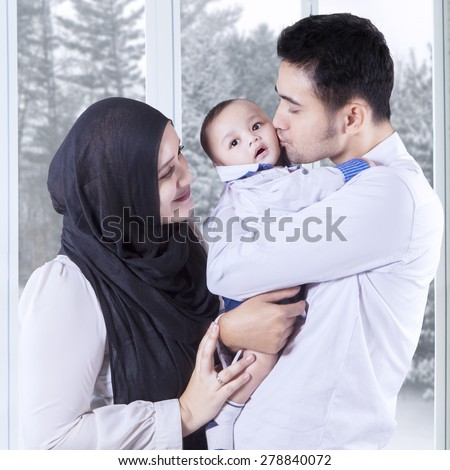 Portrait of happy parents hugging their little baby at home, shot with winter background on the window - stock photo
