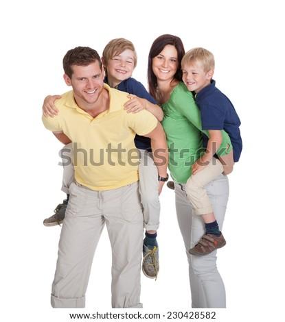 Portrait of happy parents piggybacking children against white background - stock photo