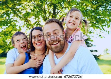 Portrait of happy parents spending time with two little children, looking at camera and smiling in park