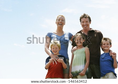 Portrait of happy parents with children standing against sky