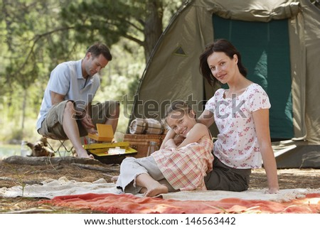 Portrait of happy parents with daughter sitting at campsite