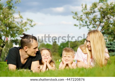 Portrait of happy parents with kids lying at the park - stock photo