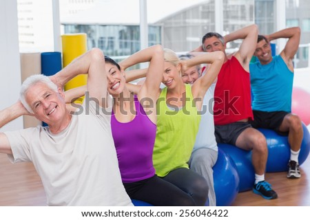 Portrait of happy people on fitness balls exercising in gym class - stock photo
