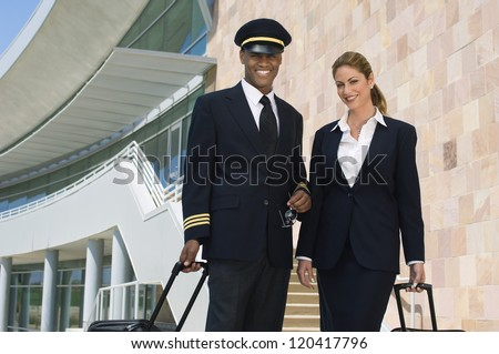 Portrait of happy pilot and air hostess standing together with luggage at the airport - stock photo