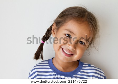 portrait of happy, positive, smiling, playful asian caucasian girl - stock photo