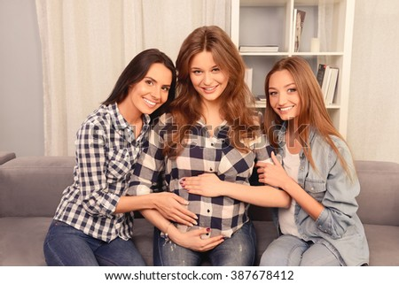 Portrait of happy pregnant girl sitting on sofa with her girlfriends
