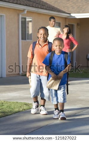 Portrait of happy preteen boys walking together with parents in the background - stock photo